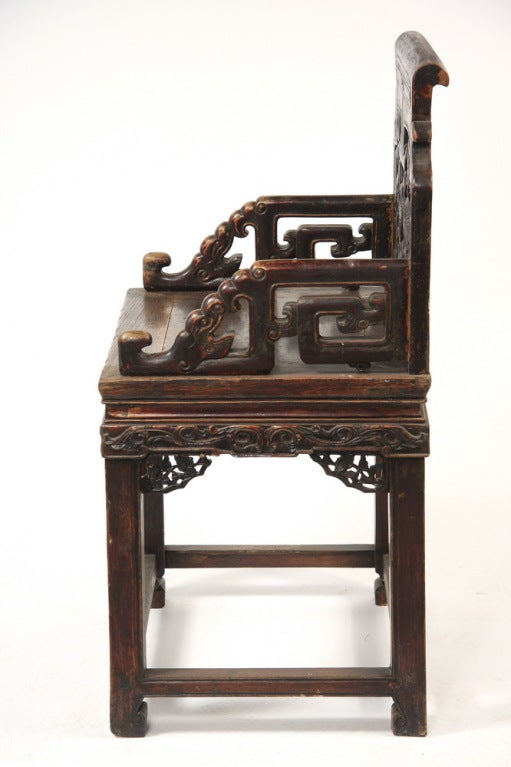 A good pair of Chinese carved walnut wood (hetao mu) armchairs.   The back features two facing stylized dragons around a central shou (longevity) medallion below a scrolled crest rail. The arms are also carved as stylized dragons. The solid plank