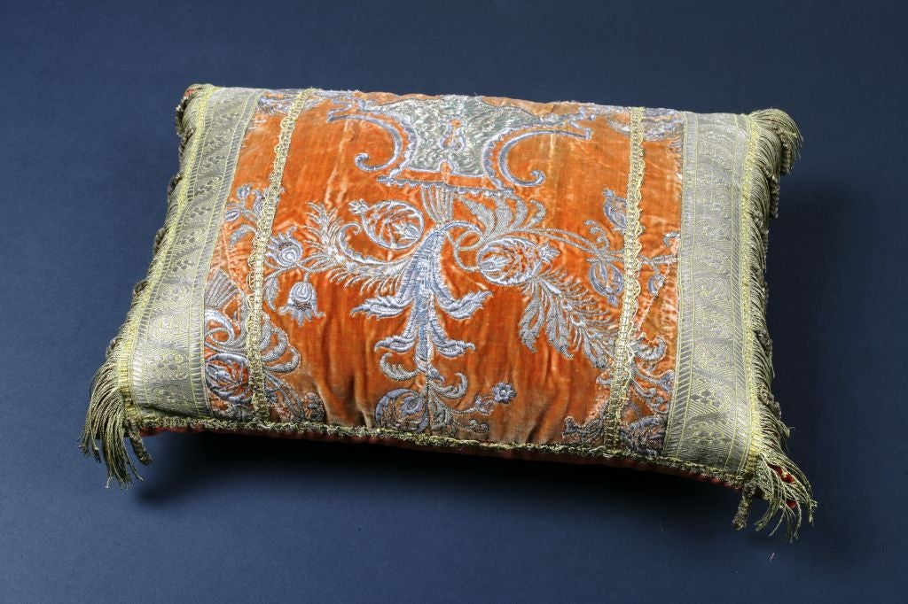 An antique Ottoman Empire textile fragment of rich burnt orange silk velvet with silver metallic micro-embroidery made into a pillow.