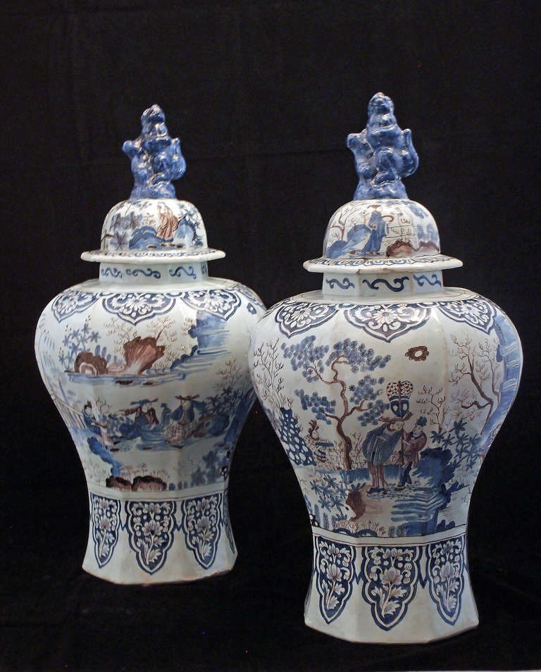 A rare and impressive pair of faceted covered baluster jars painted in underglaze cobalt blue and manganese red in the Ming transitional style with scenes of courtiers and attendants in a garden landscape of trees, rocky outcrops and clouds, with a