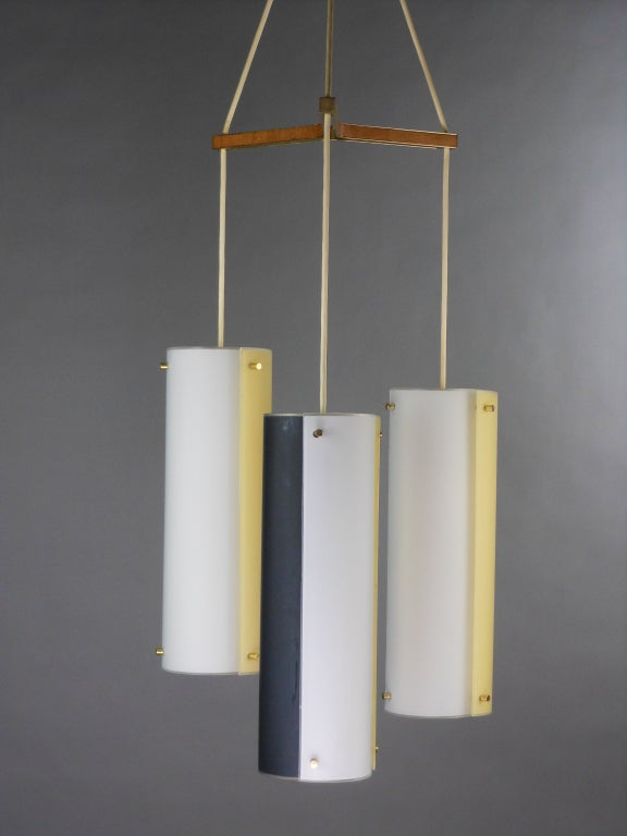 The chandelier's circular corona issues three cylinder hanging lights, separated by a tripartite boomerang form stretcher. The Italian glass lights each have three blue, white and yellow concave rectangular panels.  Each cylinder is 18 inches high