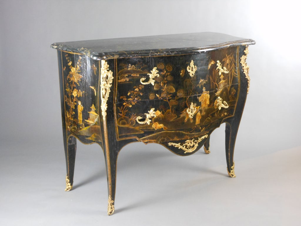 This beautiful 18th century commode has two drawers sans traverse and slender cabriole legs. It is mounted with gilt bronze foliate handles, escutcheons and sabots. The chinoiserie lacquer scenes depict figures in an exotic landscape with pavilions.