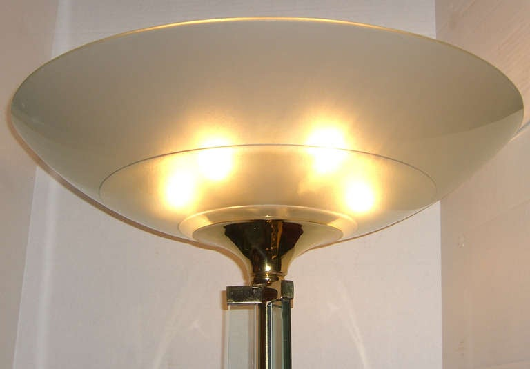 A pair of French up light standing lamps comprised of three 1/2 inch thick glass panels that surround a brass center shaft. Brass fittings attach the panels to the 3/4 inch thick glass base as well as the large circular frosted glass shade