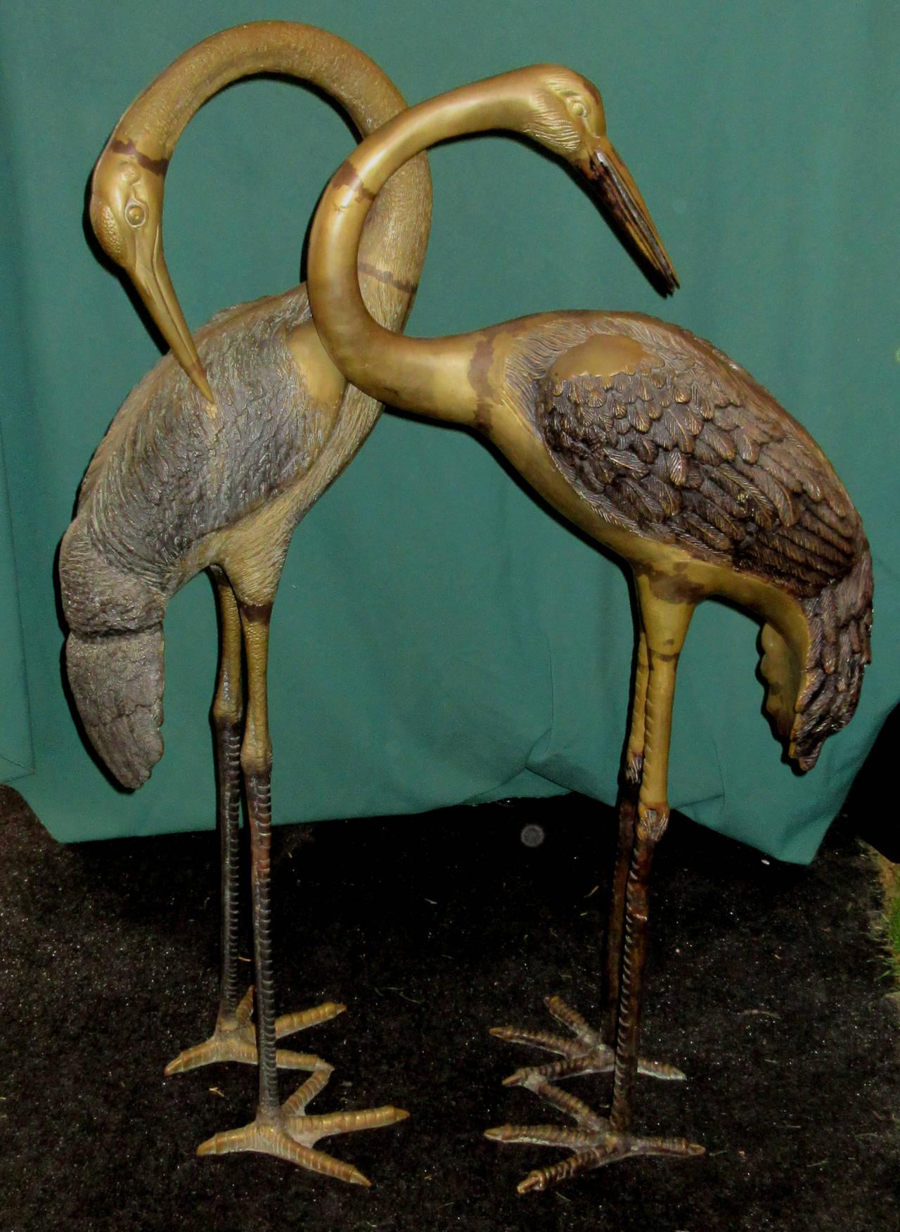 A complementary pair of cast brass standing heron sculptures.