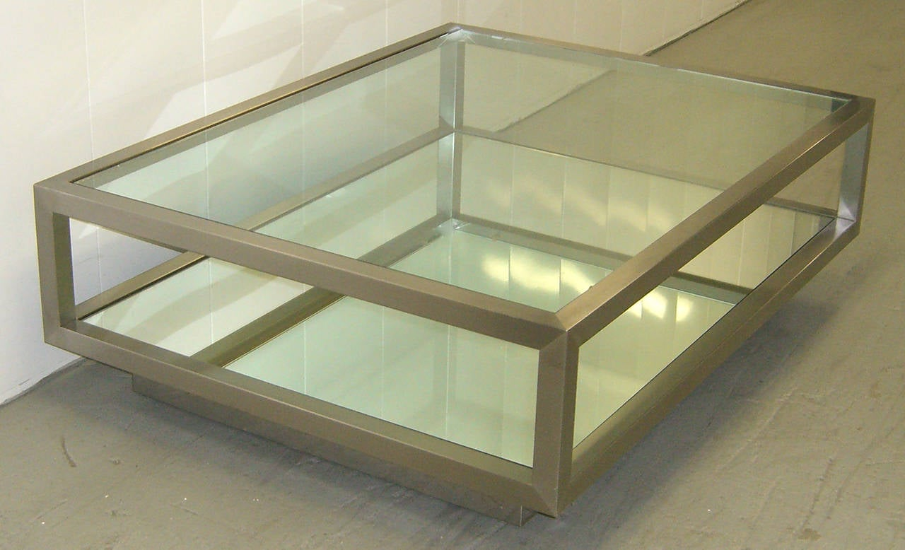 A large rectangular cocktail or coffee table of brushed steel with a glass top and mirrored lower shelf. Casters are beneath an inset platform base.