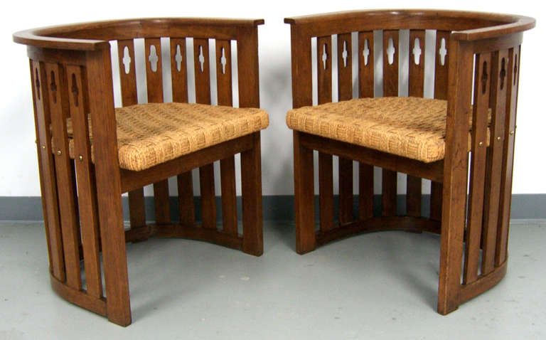This is a very special pair of barrel shape slat chairs of solid oakwood. Carved designs adorn the back and solid brass screw heads embellish each slat. The seats are the original woven jute, in very solid condition.