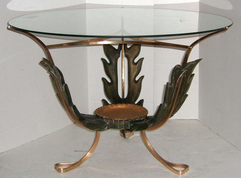 A very unique round, glass top cocktail table. The base is comprised of solid brass and a green and giltwood leaf form center.