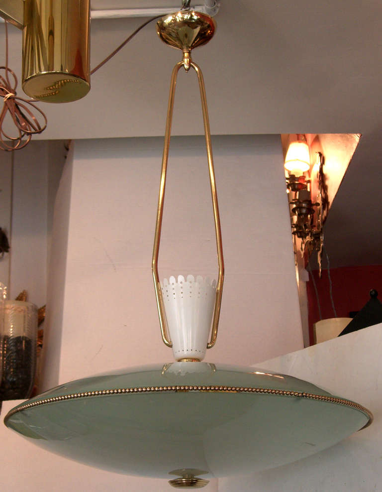 A frosted glass saucer form shade hangs from a fixed double arm. A beaded brass rim adorns the glass, and a punched white enameled metal cone tops the shade.