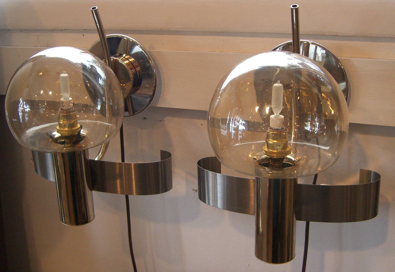 A pair of wall light or sconces of steel and gold tone metal with amber glass globes. Newly wired for the US with a chrome backing plate added. Pictured with 60 watt halogen bulbs.