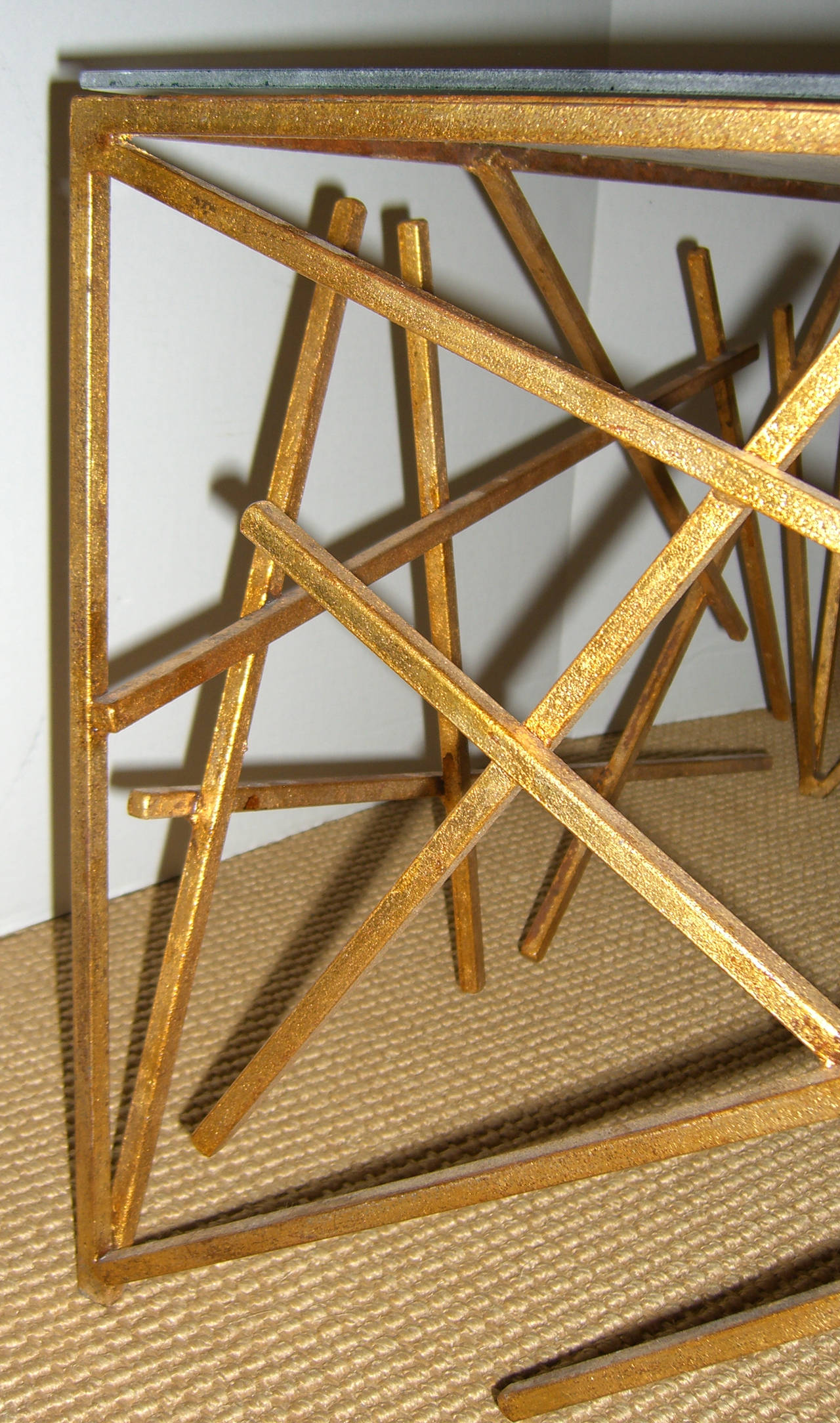 A unique table with bright gold criss-cross base and copper tone patinated steel top. Glass has been added to protect the finish.
