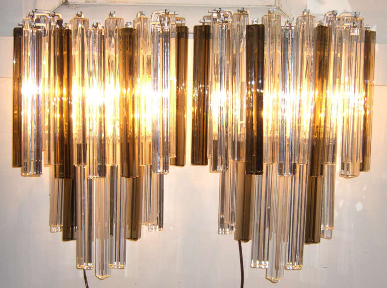 Large Venini glass prisms in a combination of clear and smoked. The glass triedri prisms alternate in height to create a Cascade effect. The sconces are lit by three newly wired candelabra sockets. A metal back plate has been added for secure