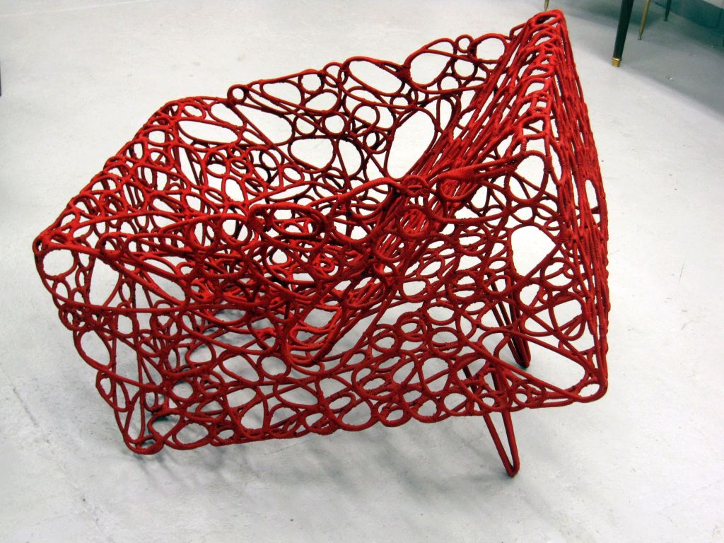 An architectural chair with a solid square form given the appearance of lightness by dozens of cut pieces of metal assembled by hand and woven in nylon fishing nets. The chair is the work of a French artist born in Mali who was inspired by