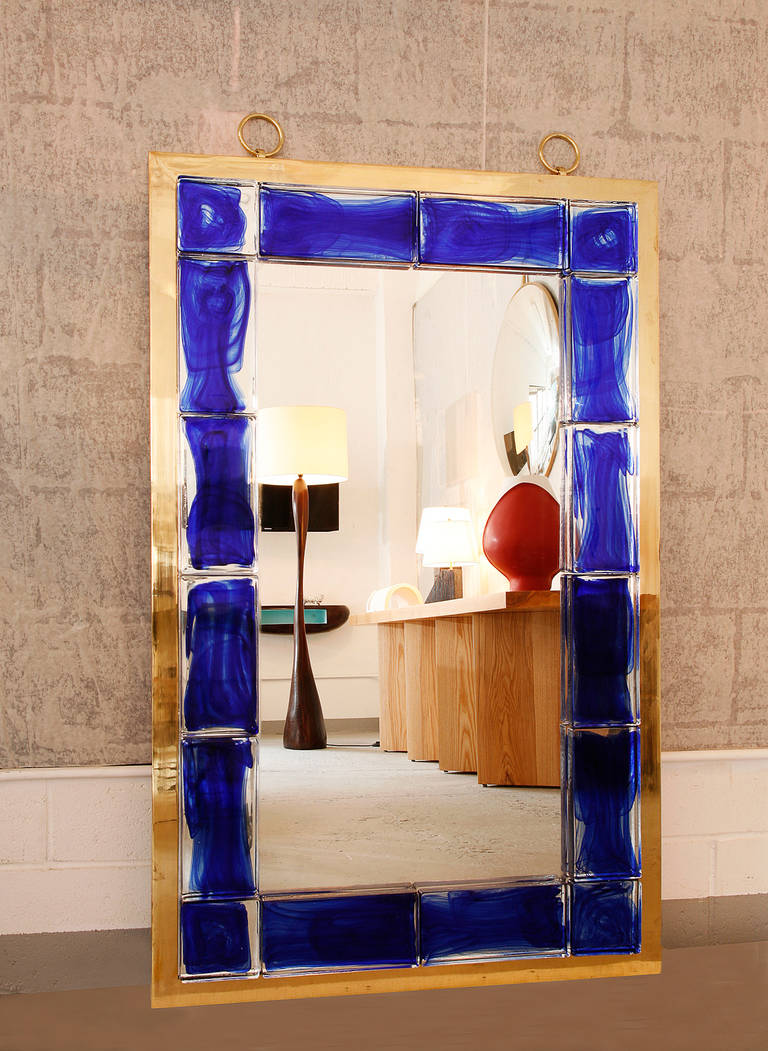 A stunning mirror with blue glass tiles and a brass frame.