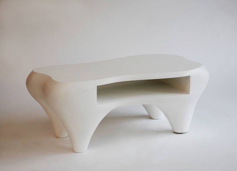 A sensual hand-sculpted coffee table with an open shelf by Jacques Jarrige. MDF sculpted with white patina.  Standing lamps by Jacques Jarrige in white lacquer. Signed.   Jarrige's work has been recently featured in IDEAT, November 2011, AD
