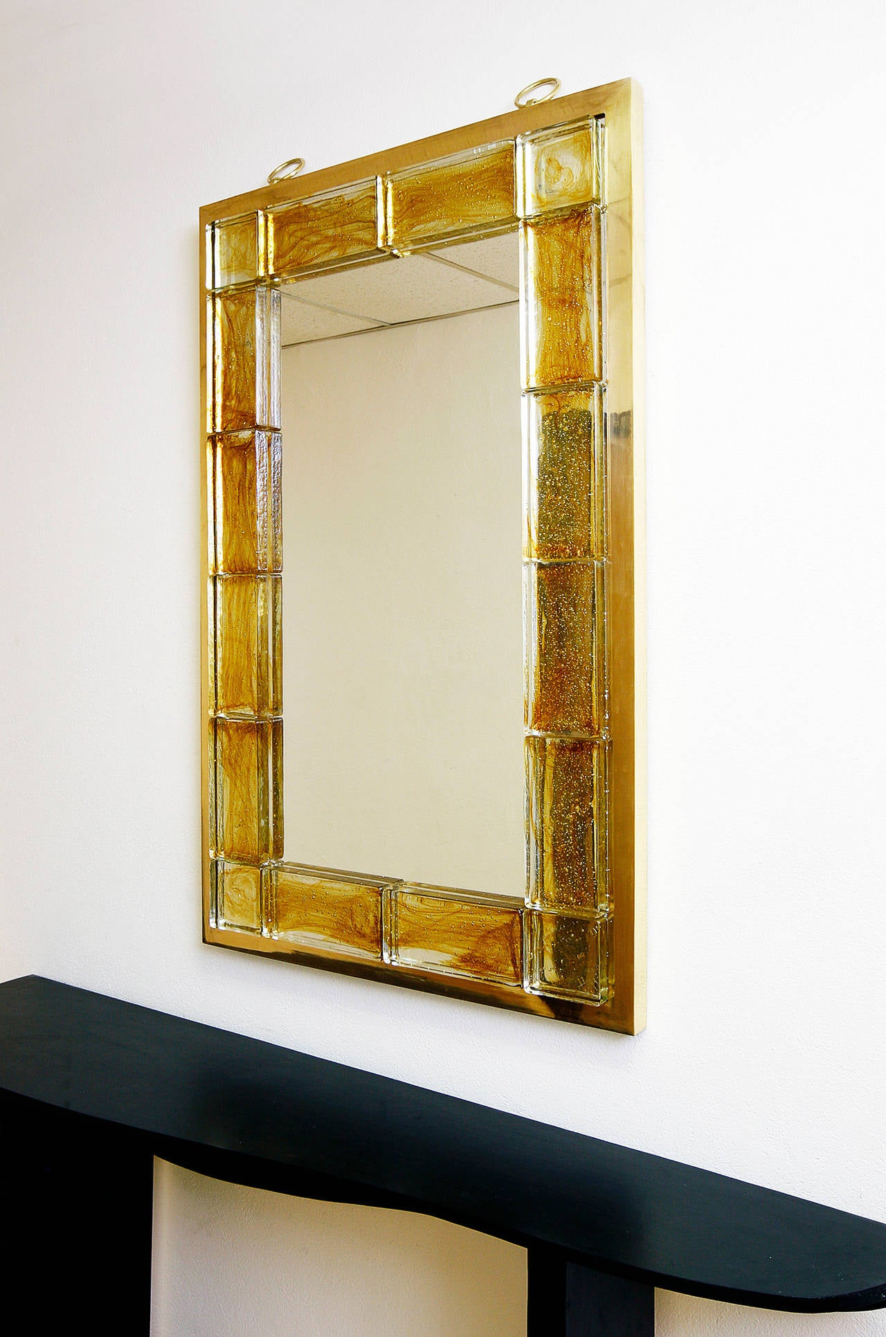 An elegant mirror by Andre Hayat with a brass exterior frame a thick glass tiles around the mirror.