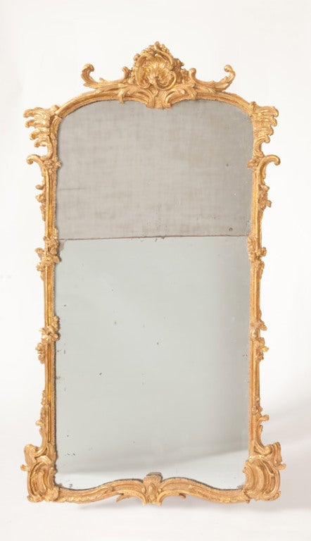 This fine French Louis XV period mirror, formerly part of a boiserie ornament, was made in rococo taste in the mid eighteenth century. The rocaille forms, C-scrolls and floral motifs are all finely carved and gilded.