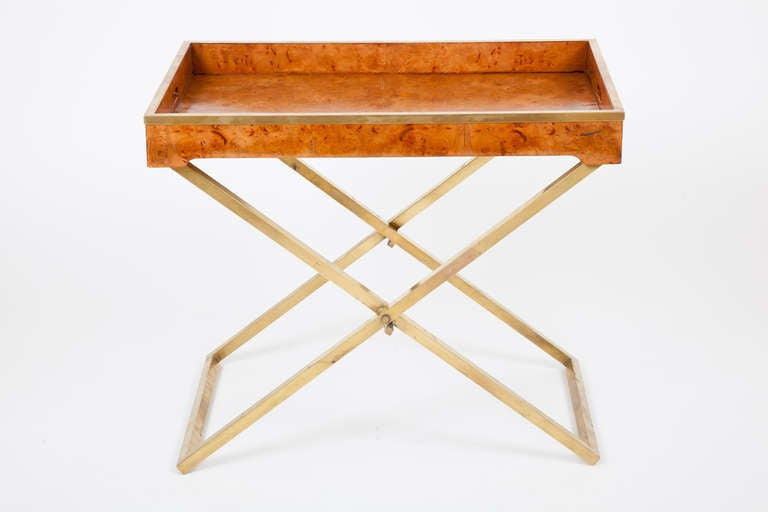 This American modern folding tray table, or butler's table, has a collapsible bronze X-form base, supporting a burl walnut tray-form top, edged with a bonze molding.