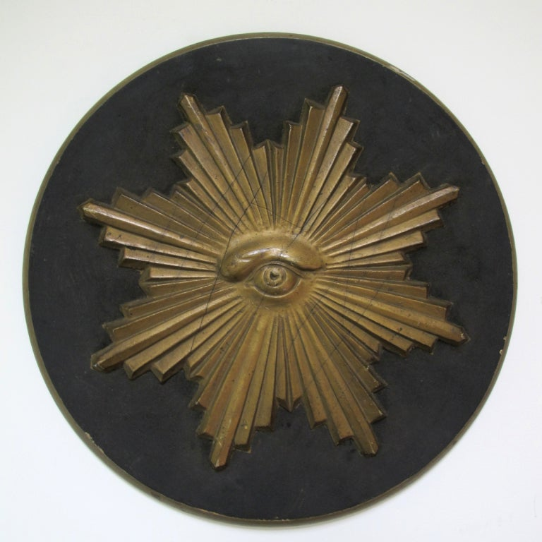 The All Seeing Eye was a symbol of carved wood from early Odd Fellows Lodge.  It has a gold painted surface and is on a black wood disc.  14 inches in diameter.
