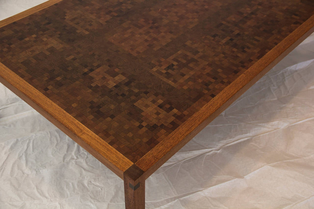A Tranekaer Studio handcrafted Danish coffee table framed in teak from the 1970s.   The top is a grid of 1800 plus one inch blocks of teak, walnut, oak, zebra and other exotic wood squares glued together forming a mosaic pattern. Very unusual not