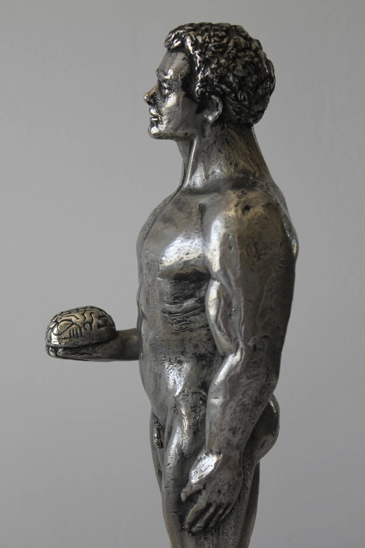 Figure of man holding brain. Called technology man on bottom of stand. This piece is more impressive in person. It weighs about 20 pounds and it's probably nickel over bronze. Figure is 4.5