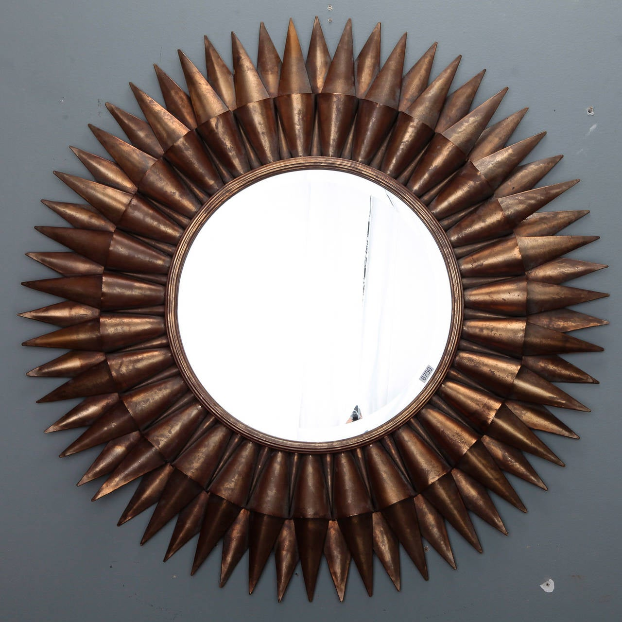 Circa 1970s Spanish sunburst mirror with a two layer frame of gilded metal rays and round center mirror.