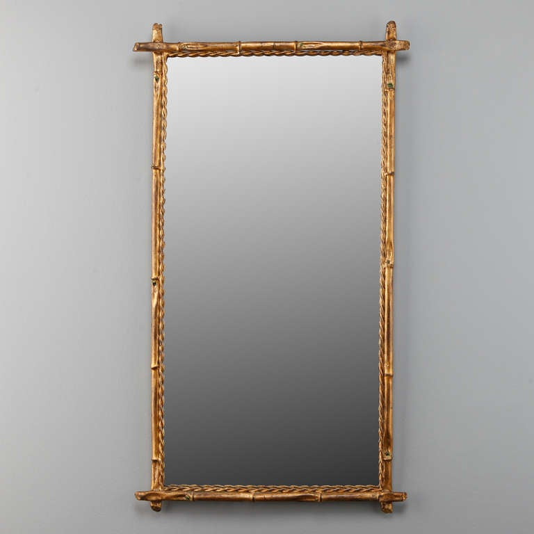 Circa 1940s Italian rectangular mirror has a faux bamboo gilt metal frame and twisted, rope style inner edge.