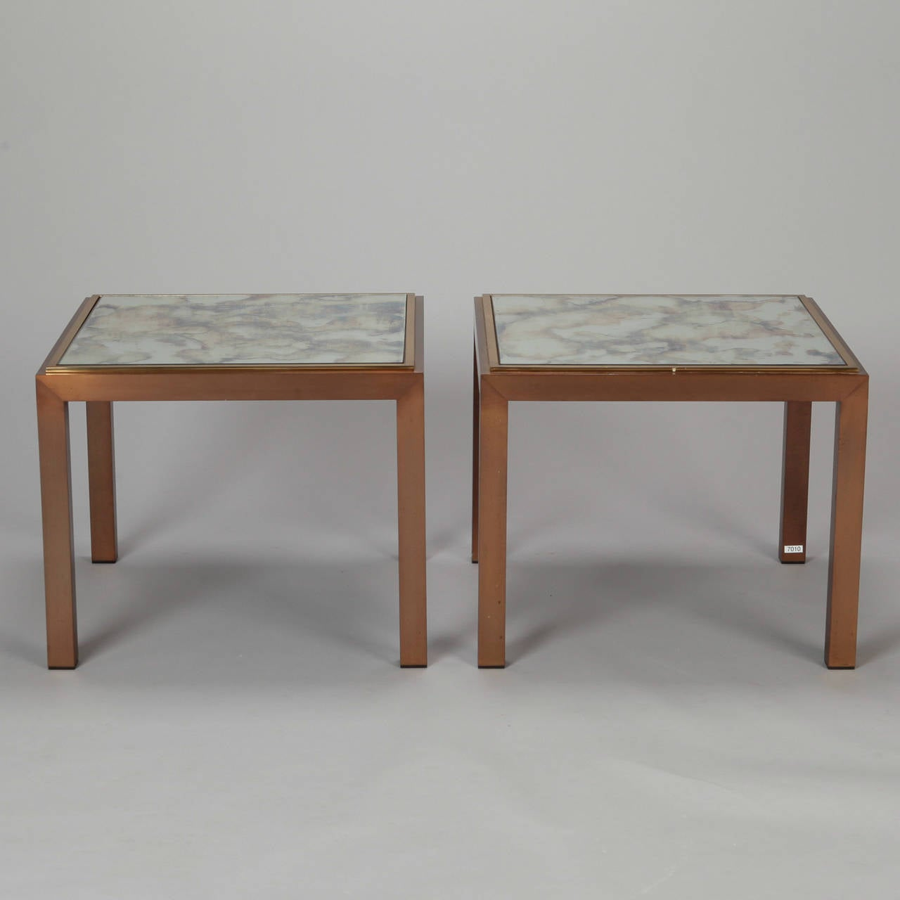 Pair of circa 1960s square end tables with streamlined bronze frames and smoke colored marbelized mirror table tops. Sold and priced as a pair.