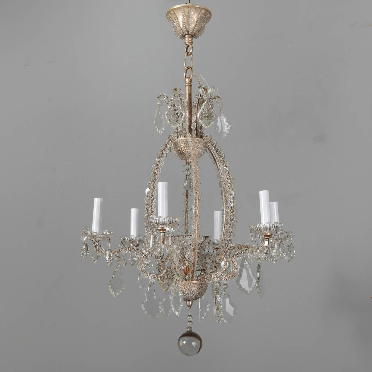 Pair of circa 1900, Italian six-light chandeliers with frames covered in clear, flower-shaped crystal beads, cut crystal bobeches, candle style lights, large crystal prisms and center drops. Original metal ceiling canopies with beaded details. New