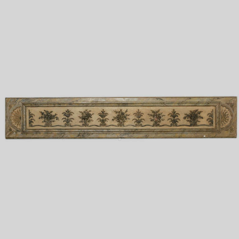Italian architectural panel with wide, decorative molding framing several carved floral arrangements and topiary forms linked at the base by a scrolling ribbon, circa 1900.