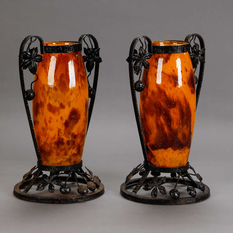 Pair of tall French art glass vases in warm tortoise and amber tone with black iron surrounds with large, curved handles and open work circular pedestal base with leaves and berries, circa 1930. Etched signature (see detail photo) Delatte Nancy.