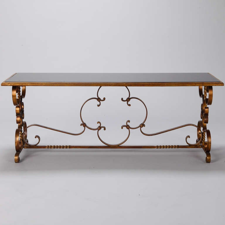 Italian low cocktail or coffee table with gilded iron base, scrolled feet and black glass tabletop, circa 1930s.