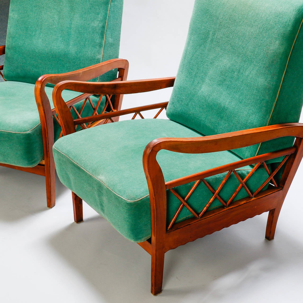 Found in Italy, this pair of circa 1960s lounge chairs feature lattice form details at the sides and curvy armrests. Seats are 15.5