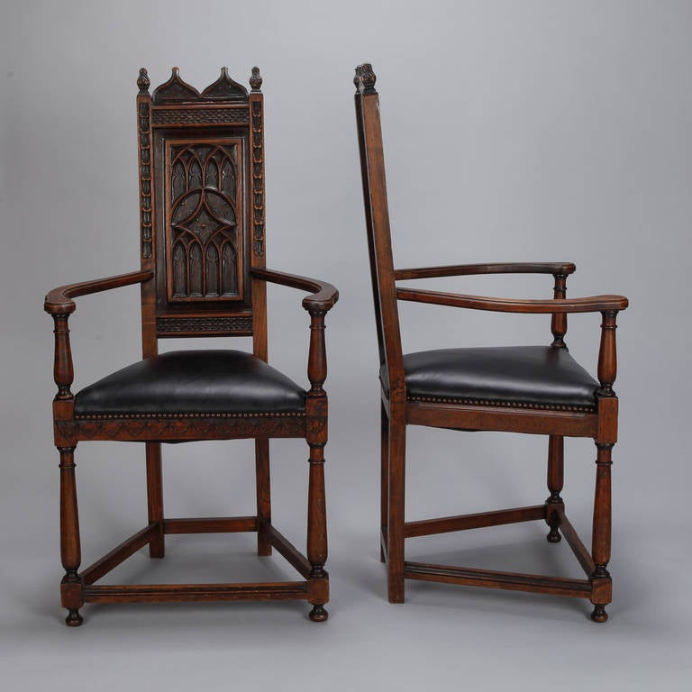 """Circa 1900 pair of French hall chairs in oak with gothic style carved details on the seat backs and upholstered in black leather. Arms are 21"""" high, seats are 21"""" high and 19"""" deep. Sold and priced as a pair."""