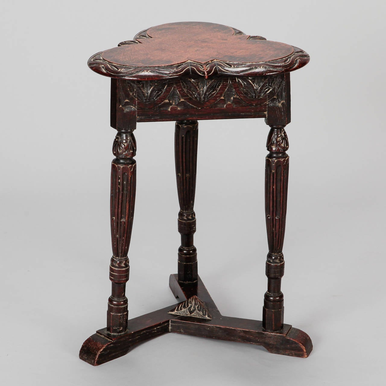Side table has a trefoil shaped top with highly carved details on apron and turned legs, circa 1890s.