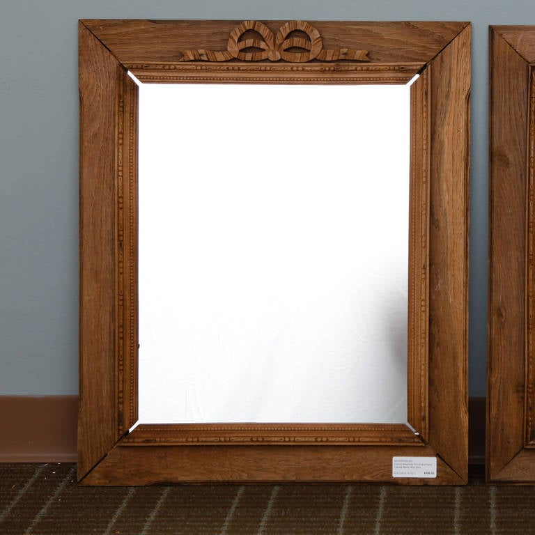 Circa 1920s French bleached wood frame mirror with carved bow and ribbon crest. Three available. Sold and priced individually.  2 = 21.75