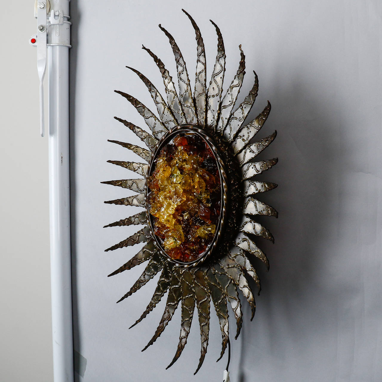 Large, circa 1970s single large sunburst or sunflower form sconce with textured metal petals and chunks of gold colored resin at the center. New wiring for US electrical standards.
