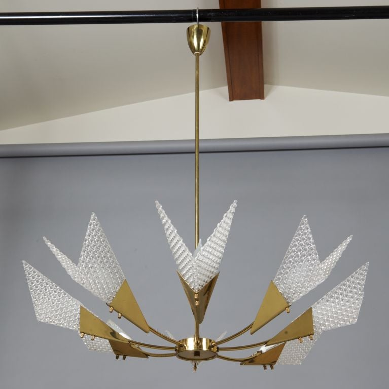 Circa 1950s European eight arm chandelier with iconic atomic / Sputnik styling. Brass frame and angular, textured acrylic globes. Fixture was found in Austria and is unmarked, but looks like German fixtures from this era.  Height shown is to top of