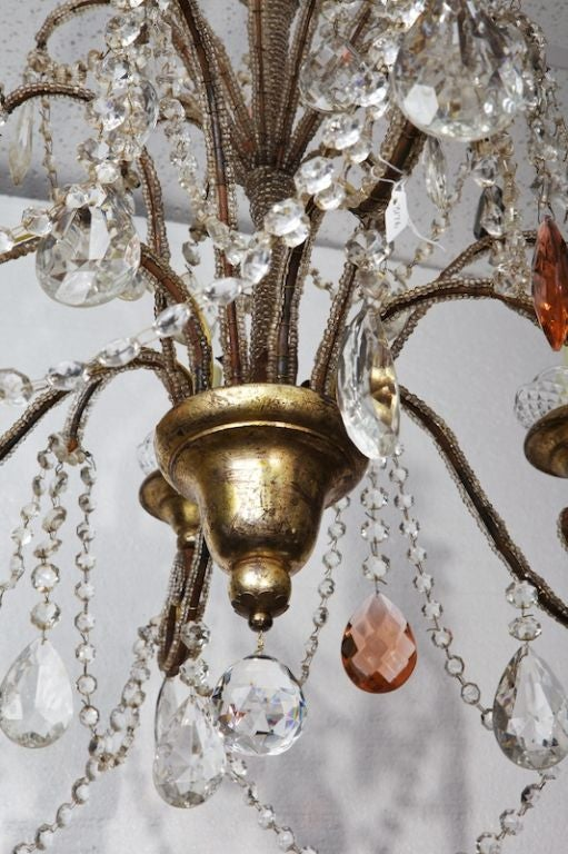 Italian six-arm chandelier dates from 1900. Giltwood base with brass beaded arms, giltwood bobeches, lots of clear faceted crystals and accented with amber and smoky blue crystals. # of Sockets: 6 Socket Type: Candelabra.