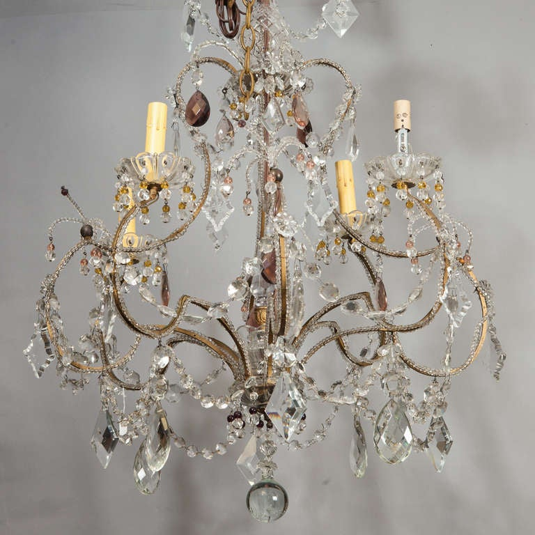 Circa 1920s French chandelier has four candle style lights, a brass cage-form base with clear glass beading, amethyst accents and several large diamond and oval shaped crystal pendants and a large round crystal drop. New wiring for US electrical
