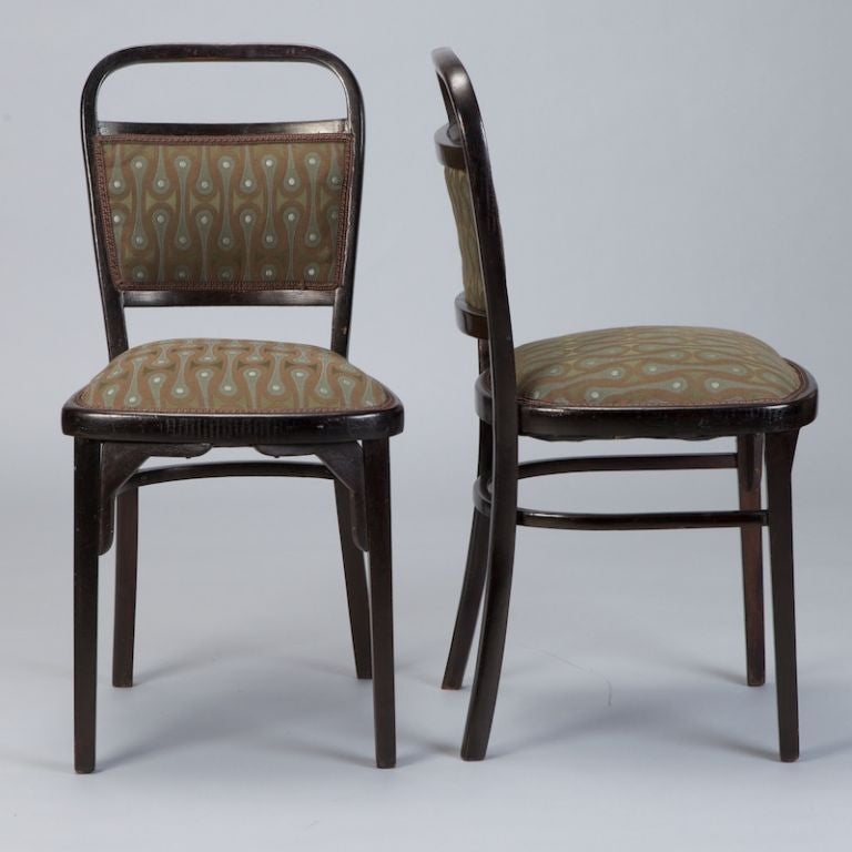 Set of four walnut Otto Wagner side chairs, dark brown stained finish, reupholstered in reproduction period material, olive, grey blue and dark taupe abstract pattern, brocade finish at seat back and seat, curved stretchers. One frame has a