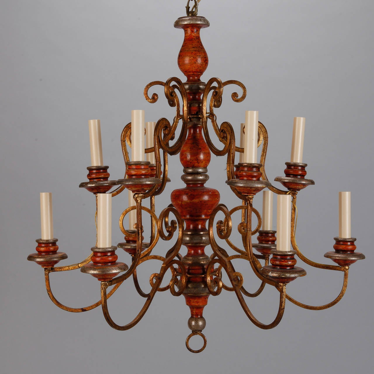 Circa 1930s twelve light chandelier from Italy with turned and wood center shaft in red painted finish, gilded iron arms and supports and wood bobeches. New electrical wiring for US standards.