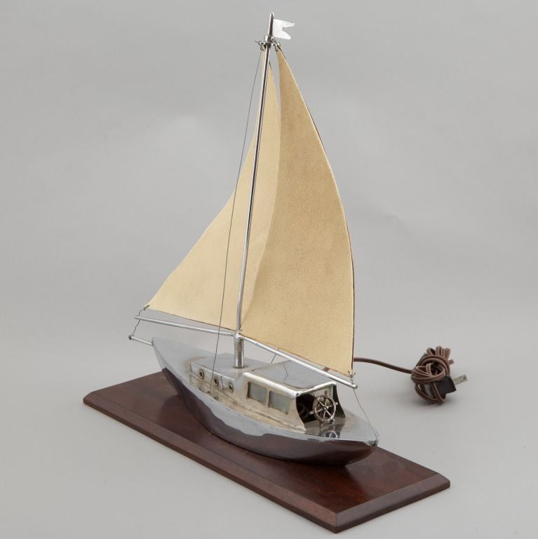 Decorative lamp is a sailboat rendered in silver tone metal mounted on wood base with shagreen and copper sail. Lightbulb located within boat cabin. Unique and decorative Art Deco piece.