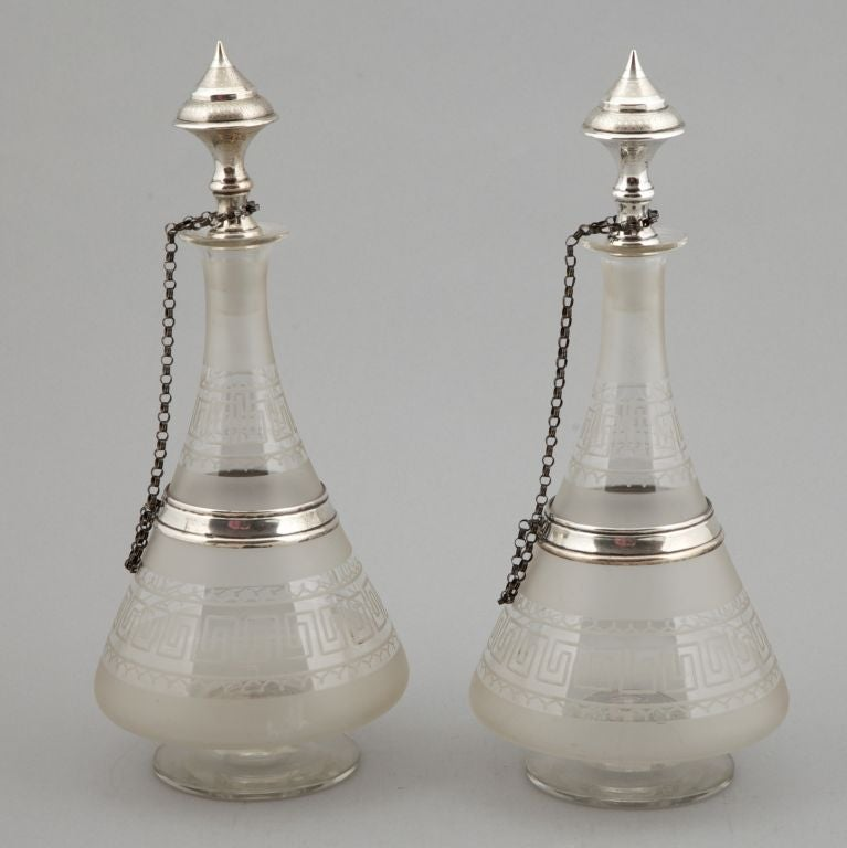 Pair of Dutch glass decanters decorated with etched Greek key design and sterling silver collars, stoppers and chains.