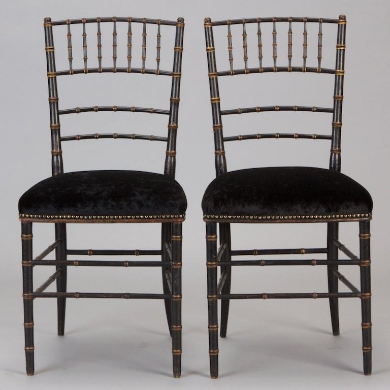 Pair of circa 1920 English side chairs with faux bamboo frames and stretchers. Chairs are finished in black paint with gilded details. Newly upholstered seats with brass nailheads. Sold and priced as a pair. Two pairs available. 