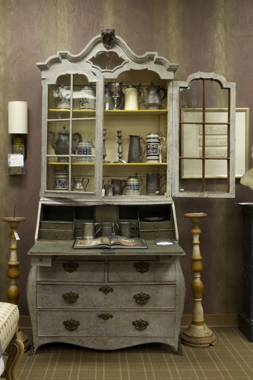 Tall late 18th century Swedish bureau bookcase with gray painted finish has top section with glass front doors, curvy crest and internal shelves. Drop down desk front has pull out supports below and four drawers with brass hardware.