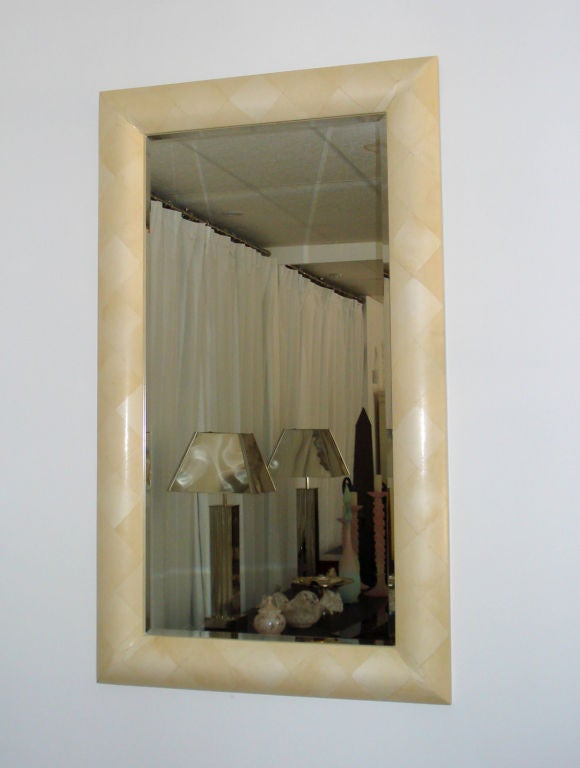 Ivory goatskin parchment cover the frame in a losange pattern with gorgeous corner cuts creating an extremely sleek mirror.