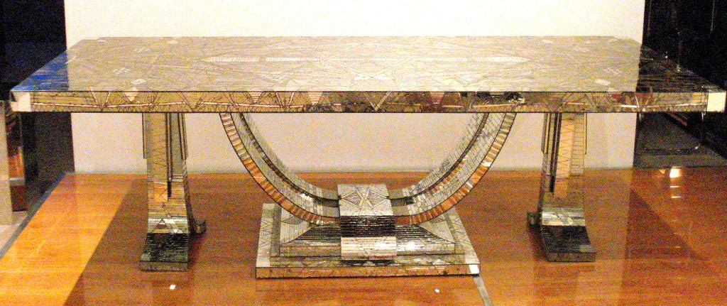 A monumental piece of art! This French Art Deco table is an example of talent. Each piece of mirror is hand cut and hand placed, forming a beautiful mosaic pattern. Two-tones of mirror are used to give the design depth. Signed Daniel Clement, 1940,