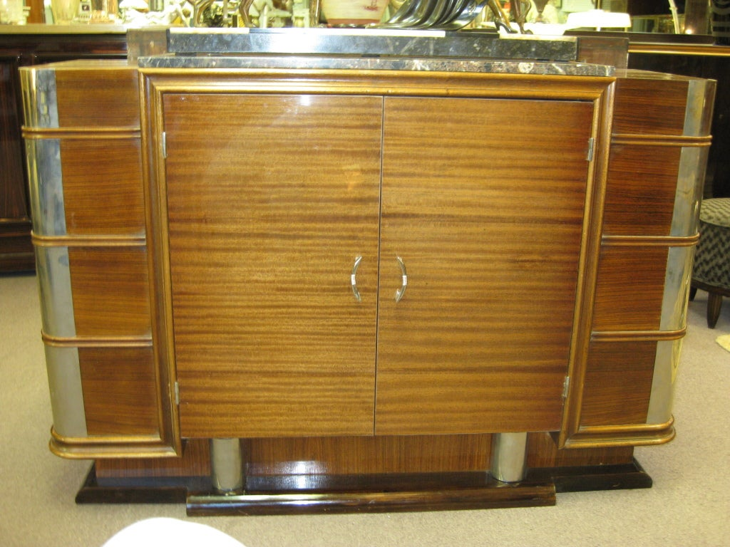 French Modernist ribbon stripe mahogany buffet, circa 1930. Unusual polished nickeled bronze mounts accent the rounded corners of this cabinet with an armour like protection. The horizontal grain echoed by the horizontal molded banding visually