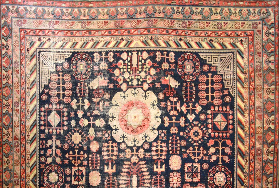 Beautiful Khotan Rug with unique medallions and tree of life pattern throughout. The border is beautifully detailed with colorful stripes and pomegranite symbols. This is a large rug, rare for this style of Khotan.