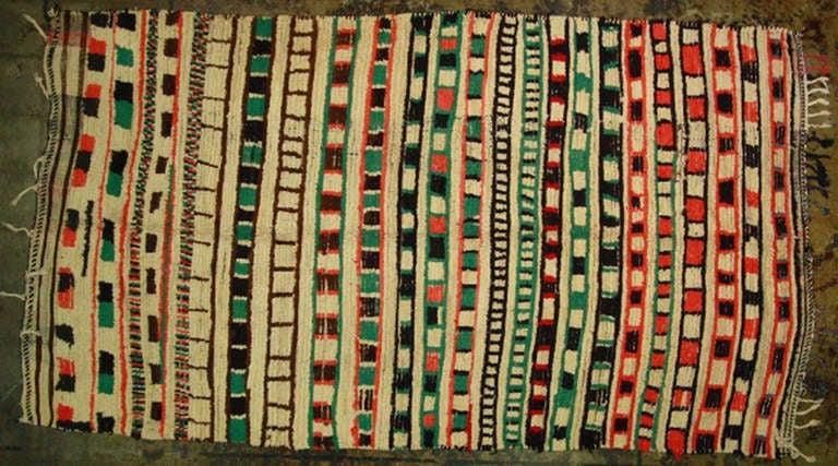 Mid-Century vintage Moroccan rug. Has beautiful geometric shapes in beautiful hues of green, red and black. 100% wool.