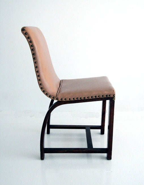 A set of four chairs designed in 1930s by Gilbert Rohde for Heywood Wakefield Gardener MA. Mahogany construction with arched back support. Cream upholstery with brass nail taps is likely original. All labeled.